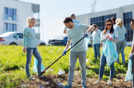 šťastný: dobrovolnictví, charita, čištění, lidé a ekologie koncept - skupina šťastných dobrovolníků s pytle na odpadky čištění plochy v parku