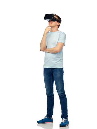 entertainment concept: 3d technology, virtual reality, entertainment, cyberspace and people concept - happy young man with virtual reality headset or 3d glasses thinking