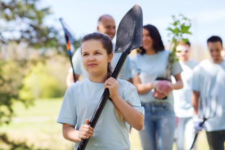 il volontariato, la carità, la gente e concetto di ecologia - gruppo di volontari felici con piantine di alberi e rastrello a piedi nel parco