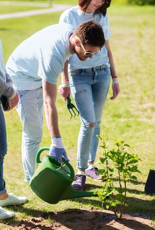 selfless: volunteering, charity, people and ecology concept - group of happy volunteers planting and watering tree with can in park