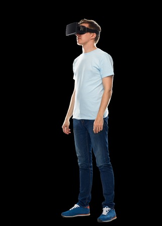 entertainment concept: 3d technology, virtual reality, entertainment, cyberspace and people concept - happy young man with virtual reality headset or 3d glasses Stock Photo