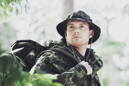war, hiking, army and people concept - young soldier or ranger with backpack in forest Stock Photo