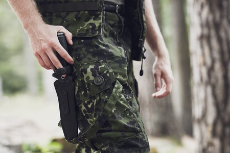 young knife: war, army, cold steel arms and people concept - close up of young soldier, ranger or hunter holding hand on knife walking in forest
