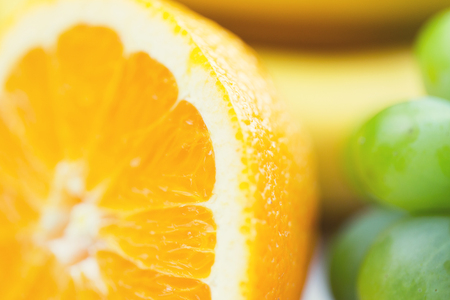 healthy eating, food, fruits and diet concept - close up of fresh juicy orange and grape