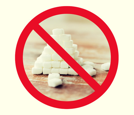 junkfood: food, junk-food, diet and unhealthy eating concept - close up of white sugar pyramid on wooden table over red circle-backslash no sign Stock Photo