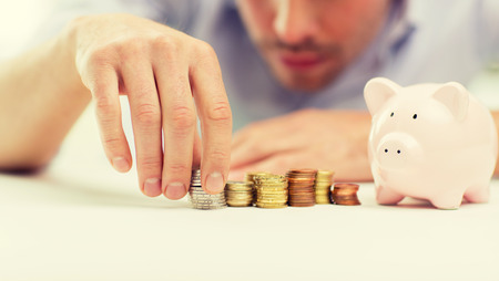 business, people, finances and money saving concept - close up of businessman with piggy bank and coins Stock Photo