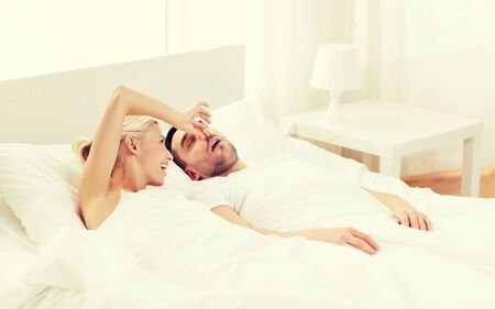 closing: people, family, bedtime and couple concept - happy woman closing nose to her snoring man sleeping in bed at home Stock Photo