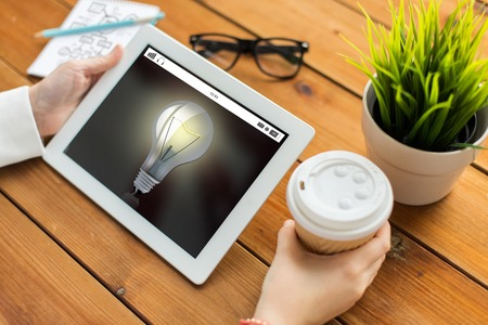 distance: business, education, technology, people and inspiration concept - close up of woman with light bulb on tablet pc computer screen and coffee cup on wooden table Stock Photo