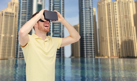 mediated: 3d technology, virtual reality, entertainment and people concept - happy young man with virtual reality headset or 3d glasses over dubai city infinity edge pool background