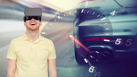 mediated: 3d technology, virtual reality, entertainment and people concept - happy young man with virtual reality headset or 3d glasses playing car racing game over tachometer and street race background Stock Photo