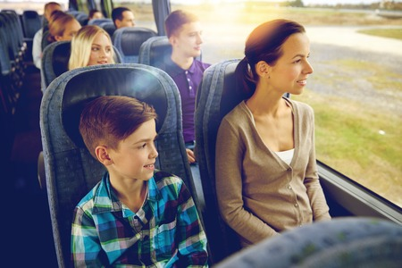public transport: travel, tourism, family, technology and people concept - happy mother and son riding in travel bus Stock Photo