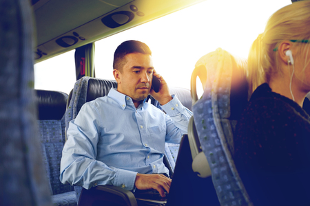 transport, tourism, business trip and people concept - man with smartphone and laptop calling in travel bus Zdjęcie Seryjne