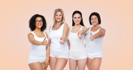gesture, friendship, beauty, body positive and people concept - group of happy different women in white underwear showing thumbs up over beige background Stock Photo