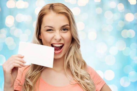 persona feliz: anuncio, invitación, el mensaje y la gente concepto - mujer joven o adolescente con la tarjeta en blanco de papel blanco sobre días de fiesta azul sonriendo fondo de las luces