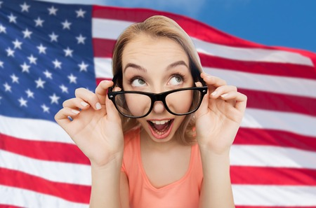 national, education and people concept - happy surprised young woman or teenage girl eyeglasses over american flag background