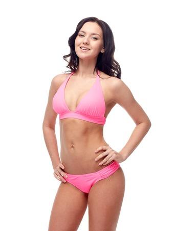 pink posing: people, fashion, swimwear, summer and beach concept - happy young woman posing in pink bikini swimsuit