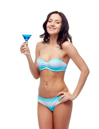 booze: people, summer holidays, celebration, drinks and beach concept - happy young woman in bikini swimsuit drinking cocktail at party