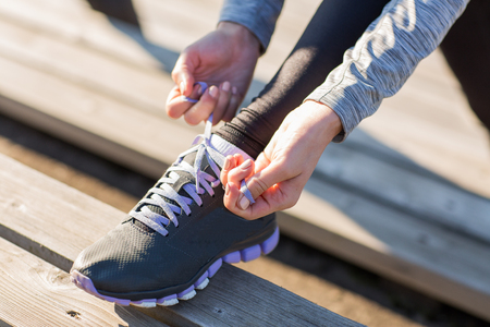 urban people: fitness, sport, people and lifestyle concept - close up of young sporty woman tying shoelaces outdoors