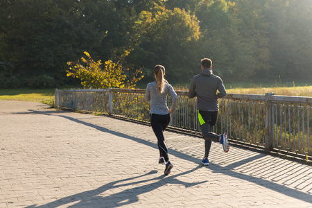 fitness, sport, people and jogging concept - couple running outdoors