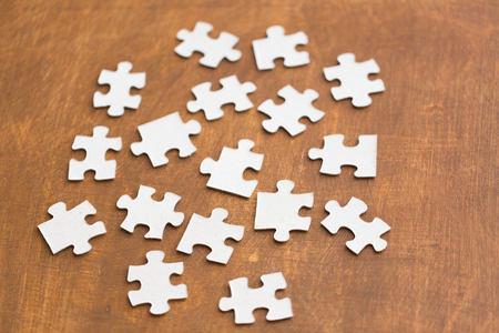 disconnection: business and connection concept - close up of puzzle pieces on wooden surface