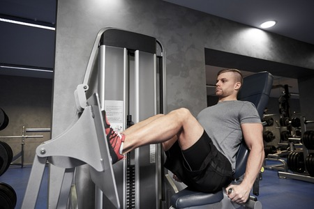healthy men: sport, fitness, bodybuilding, lifestyle and people concept - man exercising and flexing leg muscles on gym machine