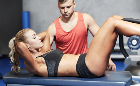 situp: fitness, sport, training, gym and lifestyle concept - woman with personal trainer doing sit ups in gym