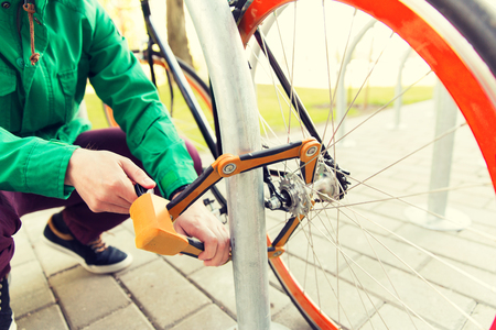 mensen, mensen, beveiliging, veiligheid en vervoer - close-up van man bevestigingssystemen fietsslot op straat parkeren Stockfoto