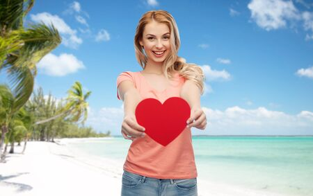 love, travel, tourism, valentines day and people concept - smiling young woman or teenage girl with blank red heart shape over exotic tropical beach with palm trees background Stock Photo