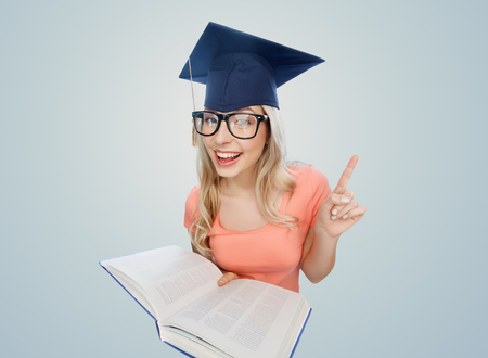 the encyclopedia: people, education, knowledge and graduation concept - smiling young student woman in mortarboard and eyeglasses with encyclopedia book pointing finger up over gray background