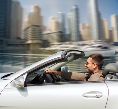 Auto zaken, vervoer, vrije tijd en mensen concept - gelukkig man rijden cabriolet auto over Dubai City Port achtergrond