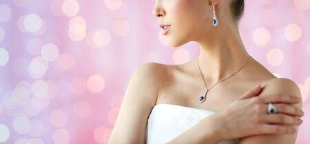 anillo de boda: belleza, joyería, las personas y el concepto de lujo - hermosa mujer asiática o la novia con el pendiente, el anillo del dedo y colgante sobre el fondo de las luces de fiesta