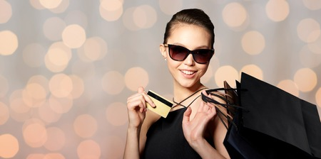 sale, finances, fashion, people and luxury concept - happy beautiful young woman in black sunglasses with credit card and shopping bags over holidays lights background Stock Photo