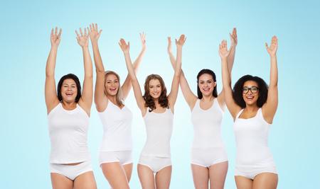 Felicidad, amistad, belleza, cuerpo positivo y concepto de la gente - grupo de felices diferentes mujeres en ropa interior blanca con los brazos levantados celebrando la victoria sobre fondo azul