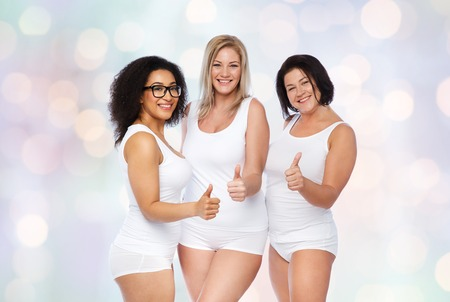 gesture, friendship, beauty, body positive and people concept - group of happy plus size women in white underwear showing thumbs up over holidays lights background