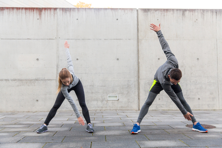 lean out: fitness, sport, exercising, training and people concept - close up of couple stretching on city street Stock Photo