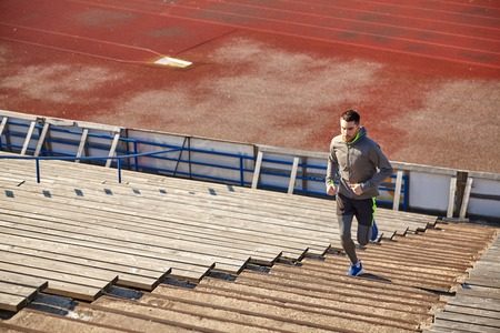 upstairs: fitness, sport, exercising and people concept - happy young man running upstairs on stadium