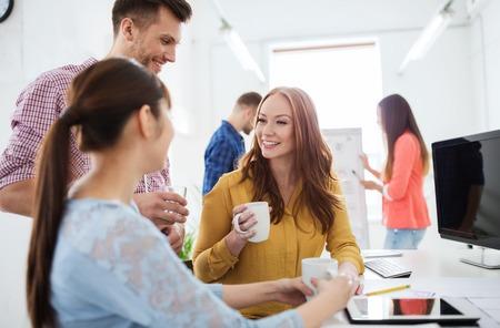 Unternehmen, Start-up und Menschen Konzept - glücklich kreatives Team oder Studenten trinken Kaffee im Büro