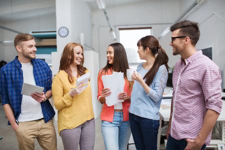 negocios, comunicación, puesta en marcha y el concepto de la gente - feliz equipo creativo internacional o estudiantes en vacaciones de café, hablando en la oficina