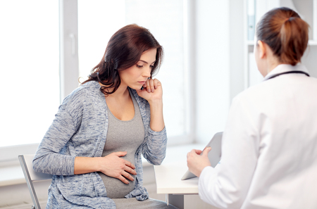 gynaecology: pregnancy, gynecology, medicine, health care and people concept - gynecologist doctor with tablet pc computer and pregnant woman meeting at hospital