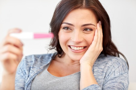 fem: pregnancy, fertility, maternity, emotions and people concept - happy smiling woman looking at pregnancy test at home