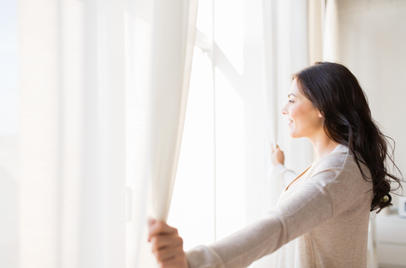 window curtain: people and hope concept - close up of happy woman opening window curtains Stock Photo