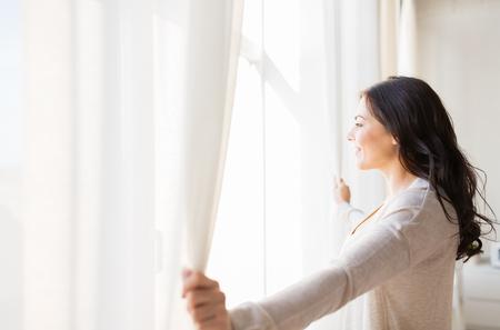 felicidade: pessoas e conceito esperança - ascendente próximo da mulher feliz de abertura cortinas de janela