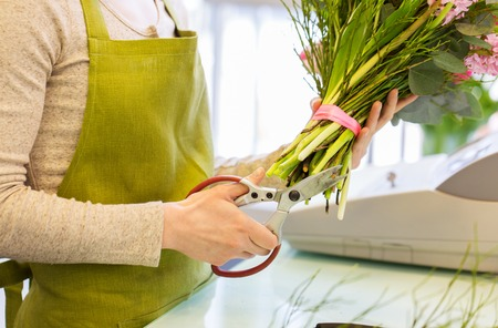people, business, sale and floristry concept - close up of florist woman making bunch and cropping stems by scissors at flower shop Imagens