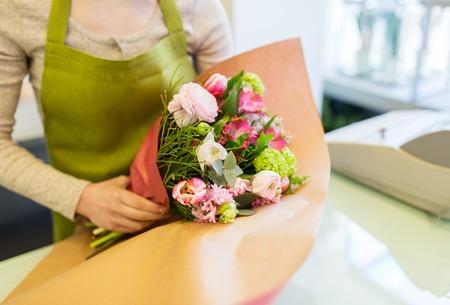 人々、ビジネス、販売、フローリストのコンセプト - フラワー ショップで紙束を包む花屋女性のクローズ アップ