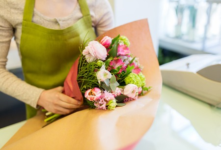 people, business, sale and floristry concept - close up of florist woman wrapping bunch into paper at flower shop Archivio Fotografico