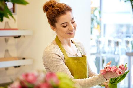 sale shop: people, business, sale and floristry concept - happy smiling florist woman making tulip bunch at flower shop