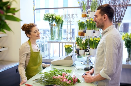 floristry: people, shopping, sale, floristry and consumerism concept - happy smiling florist woman and man or customer talking at flower shop
