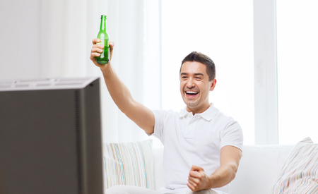 entertainment concept: home, people, technology and entertainment concept - smiling man with remote control watching tv and drinking beer at home