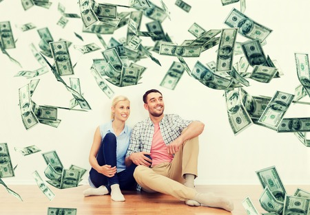 soñando: home, people, moving, finances and real estate concept - happy couple of man and woman sitting on floor and dreaming at new place over dollar money falling from above
