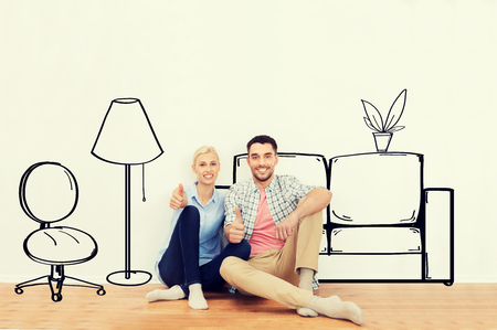 couple home: people, repair, moving in, interior and real estate concept - happy couple sitting on floor and showing thumbs up at new home over furniture cartoon or sketch background Stock Photo